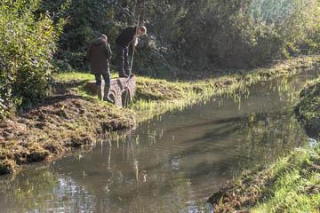 Jens Bornhöft und Hans-Peter Blohm vom Wasserverband Nettelnburg klettern auf dem Hochüberlauf vom Teich an der Randersweide zur Kampbille herum, um zu ergründen, wofür der nützt.