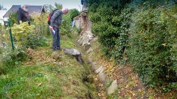 Hans Schröder vom Wasserverband Nettelnburg begutachtet eine sonderbare Böschungskontruktion aus Gehwegplatten. Ein Nachbar ist interessiert.