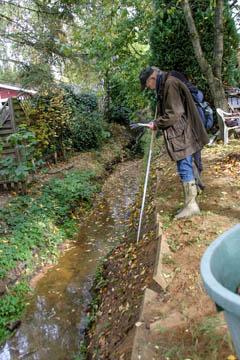 Hans-Peter Blohm vom Wasserverband Nettelnburg überlegt, ob er die schrägen Gehwegplatten an der Grabenkante so noch akzeptieren kann.