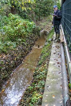 """Hans-Peter Blohm vom Wasserverband Nettelnburg am Rand einer besonderen Grabenböschung. Ein arg enger """"Schauweg"""", der hier auch noch zur Lagerung von Material verwendet wurde."""