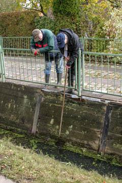 Hans-Peter Blohm und Horst Hülden vom Wasserverband Nettelnburg inspezieren die mit Holzbohlen verstärkte Böschung zum Schutz der Grundstückseinfahrt.