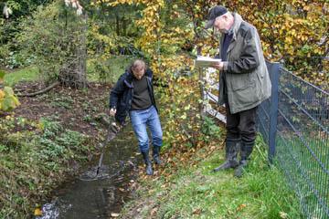 Jens Bornhöft vom Wasserverband Nettelnburg hangelt sich an einer Grabenkante entlang. Hier fehlt der Schauweg. Hans-Peter Blohm notiert.