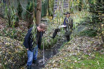 Jens Bornhöft vom Wasserverband Nettelnburg versinkt hier gerade mit seinen Gummistiefeln im Schlamm des Grabens. Hans-Peter Blohm protokolliert.