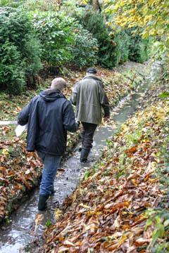 Jens Bornhöft vom Wasserverband Nettelnburg und Hans-Peter Blohm stapfen im Graben entlang.