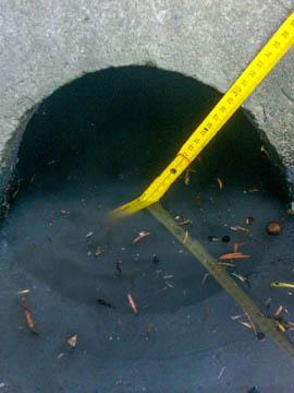 Hier wird der Durchmesser eines Verrohrung im Gebiet des Wasserverbandes Nettelnburg unter einer Einfahrt vermessen und mit den Genehmigungsunterlagen verglichen.