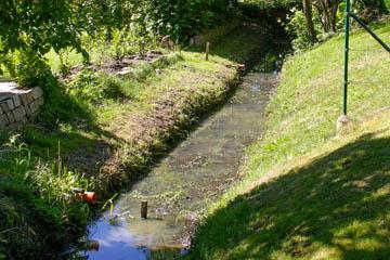Dieser Graben hat ein ideal flaches Profil, Wasser kann über den Rand laufen und hat Stauraum.