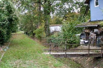 Eine Holzbrücke mit Geländer am Oberen Landweg. Stabil und sicher, keine Behinderung des Grabens.
