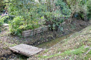 Hier eine Holzbrücke, gebaut aus Paletten mit einer Deckschicht. Sehr tief und kann den Wasserfluss möglicherweise behindern.