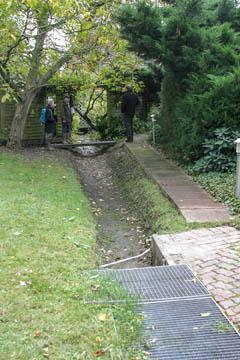 Dieser Graben wird auch durch Fahrzeuge überfahren, weil die Carports auf der anderen Grabenseite liegen. Zur Zeit gibt es wenig Alternativen zu den tiefliegenden Gitterrosten. Im Hintergrund eine Fussgängerbrücke.