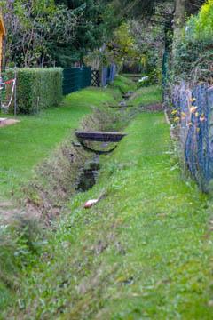 Eine ganze Brückenreihe. Da der Graben aber typischerweise fast immer ohne Wasser ist, stört hier die tiefe Lage nicht wirklich. Wenn es doch Wasserabflussprobleme geben sollte, sind nur die Anlieger und Brückenbauer selbst betroffen.