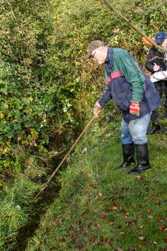 Unser ehemaliges Vorstandsmitglied Horst Hülden stochert im hohen Gras herum, um den Graben zu suchen. Vorheriges Mähen hätte hier sicherlich nötig getan.